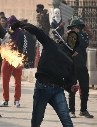 A protester throws a Molotov cocktail at police in old city Srinagar, during clashes at jamia masjid on December 21, 2018. demonstrate against the killing of seven civilians by security forces in south Kashmir's Pulwama on December 15. Stone Fire Protesters Friday Srinagar Kashmir Kashmir , India Clashes Police Force