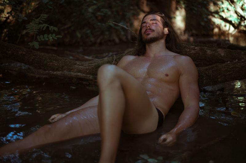 Shirtless young man sleeping by log in lake
