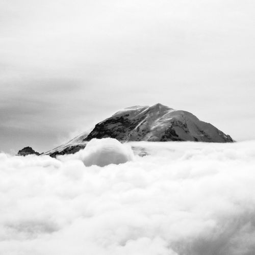 Snow covered mountain peak surrounded by clouds