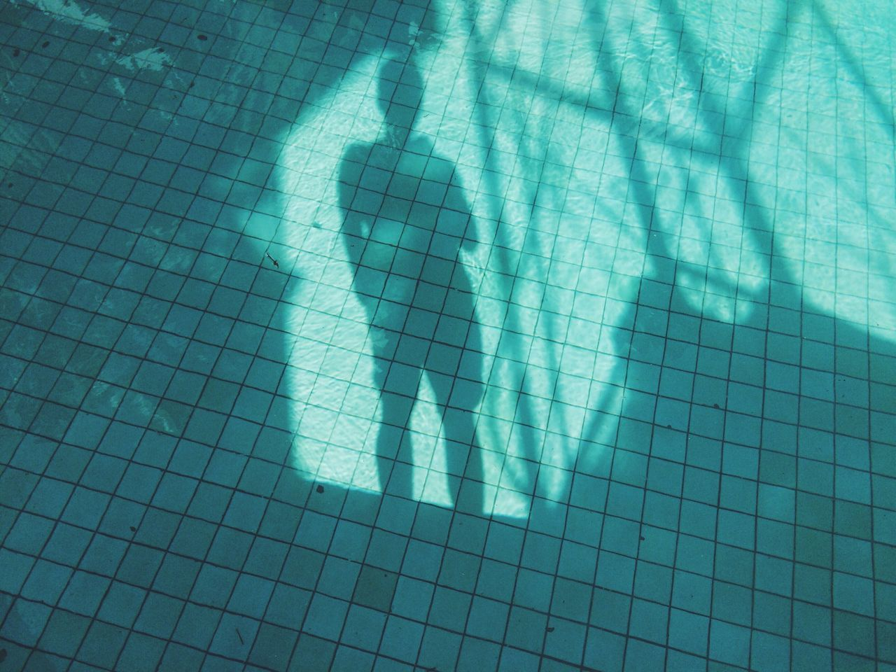 Shadow of man in swimming pool