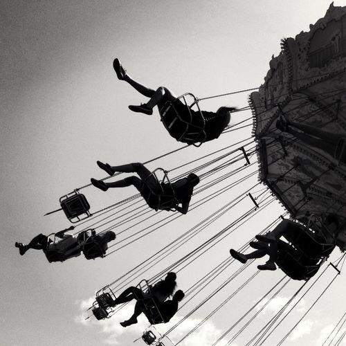 Low angle view of people enjoying chain swing ride