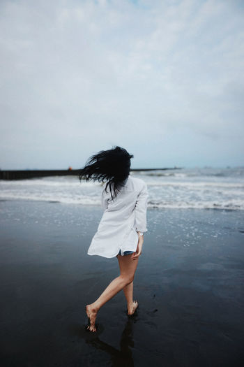 Full length of woman walking on beach against sky