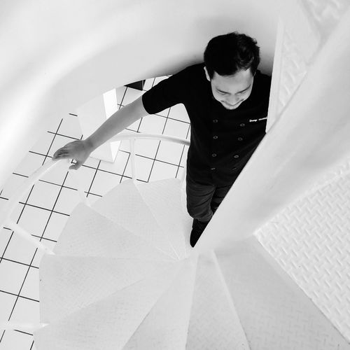 High angle view of boy standing on paper