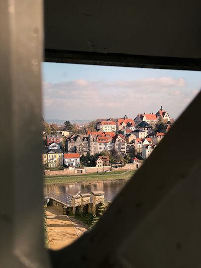 Buildings in city against sky seen through window