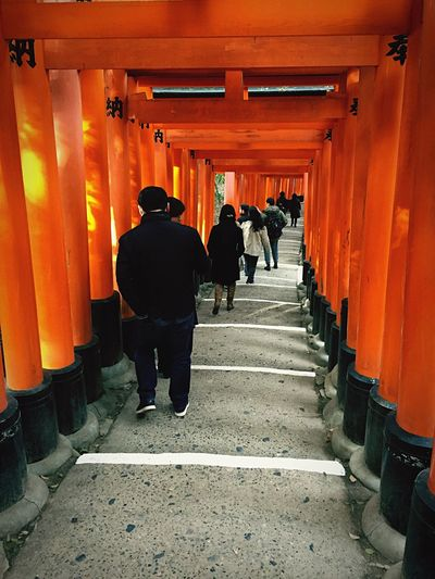 Rear View Of People Walking Inside Torii Gate