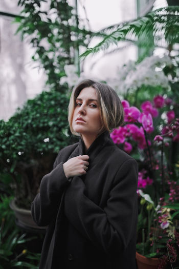 Woman looking away while standing against plants