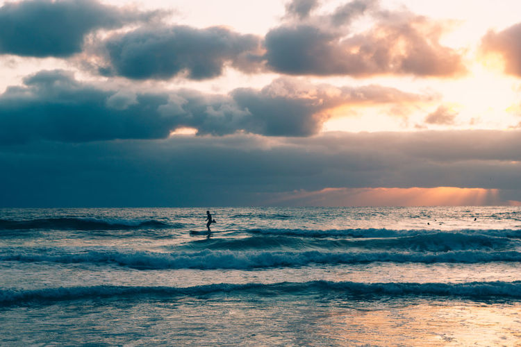 Silhouette man surfboarding on sea against cloudy sky during sunset