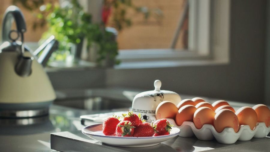Eggs in carton by strawberries and tea kettle at table