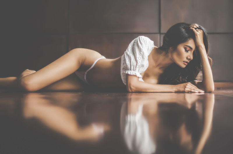 Sensuous young female model wearing lingerie while lying on tiled floor