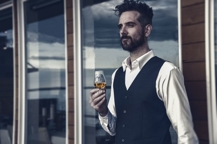 Confident man holding drink while standing against window