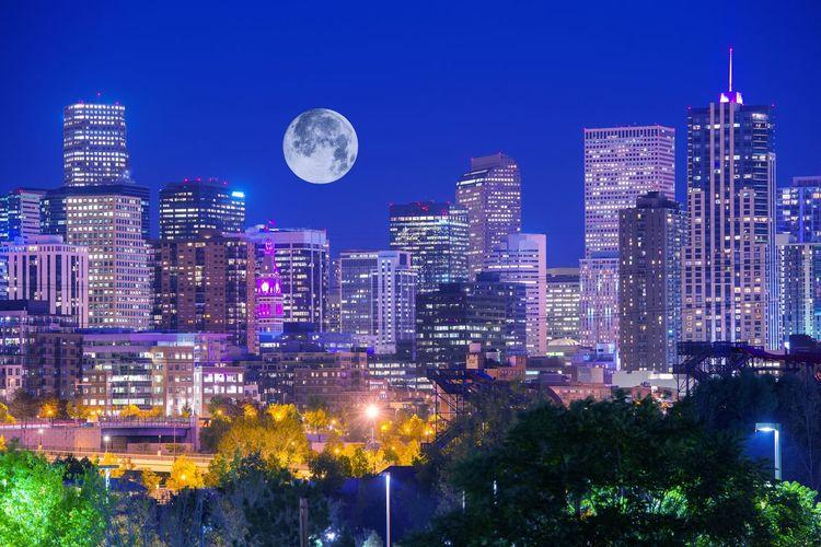 Illuminated City Against Blue Sky At Night