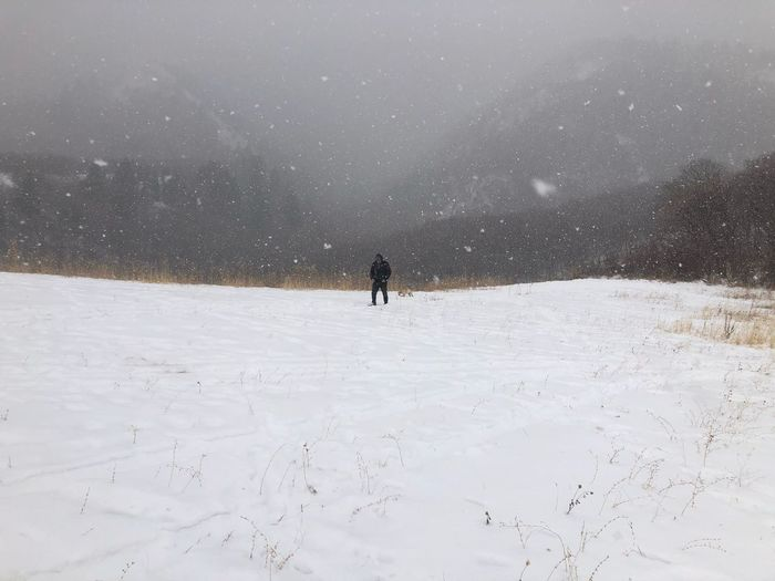 Man walking through snow storm in snow covered field