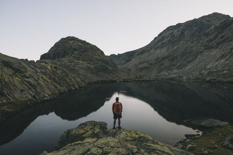 Rear view of man standing on mountain by lake against sky