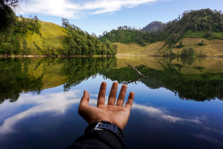 Cropped hand of man gesturing by lake against mountains