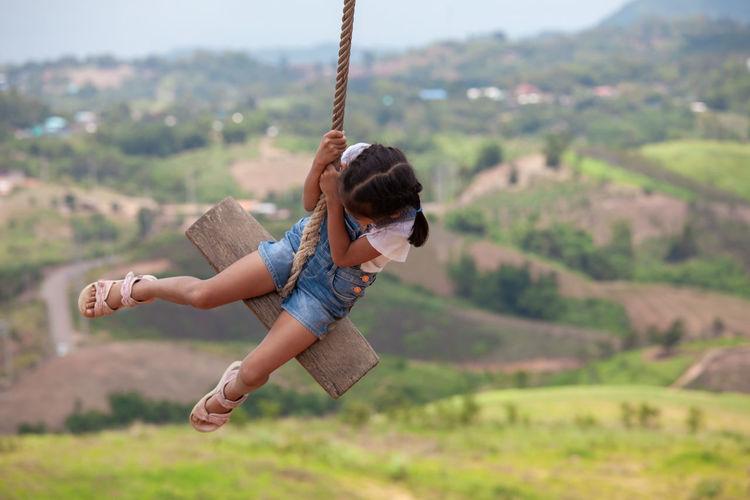 Full length of girl swinging against landscape