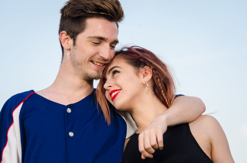 Loving Young Couple Standing Against Sky On Field