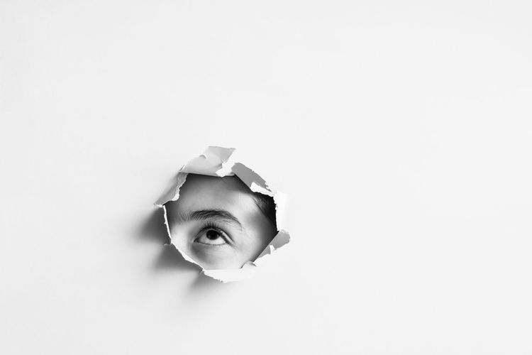 Close-up portrait of a boy peeking over white background