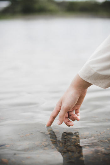 Cropped hand touching water in lake