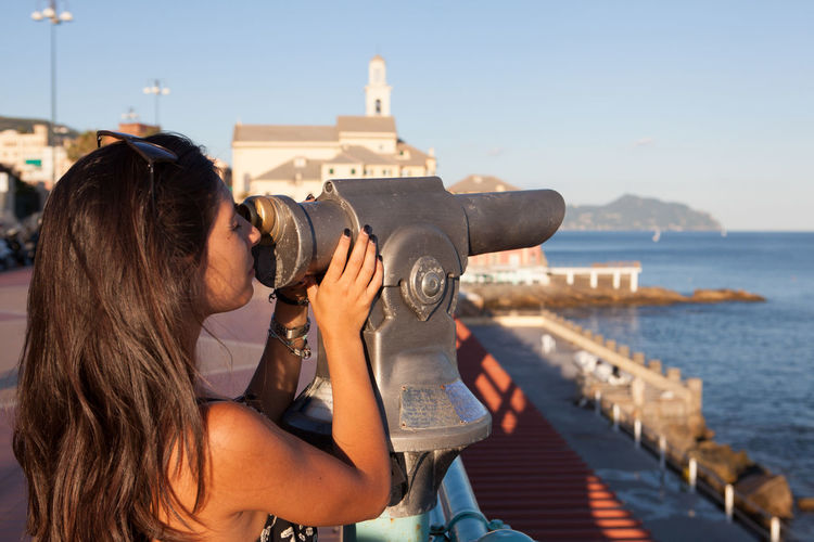 Girl tourist and panorama binoculars in Genova Boccadasse Binocular View Binoculars Boccadasse Boccadasse_genova Casual Clothing Day EyeEm Best Edits EyeEm Best Shots EyeEm Gallery Focus On Foreground Genova Girl Leisure Activity Lifestyles Outdoors Photography Themes Portofino Sky The Week On EyeEm Tourism Tourist Tourist Vacations Water Woman
