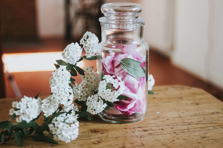 Close-up of flowers in jar on table at home