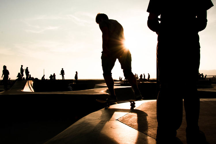 Silhouette people at skateboard park against sky during sunset
