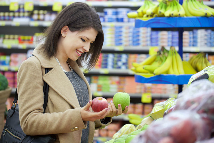 Side View Of Smiling Young Woman Holding Apples In Store