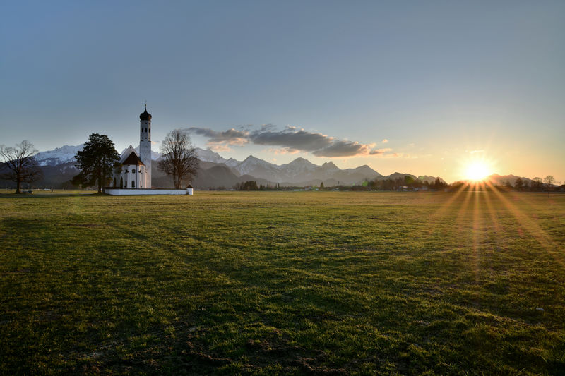 Sunset by a Bavarian Chapel in a Meadow and The Alps in Afterimage Sky Plant Sun Grass Tranquil Scene Nature Beauty In Nature Sunlight Scenics - Nature Field Land Architecture Tranquility Built Structure No People Landscape Environment Sunset Building Exterior Tree Lens Flare Outdoors EyeEm Nature Lover EyeEm Selects Travel Photography Travel Atmospheric Mood Atmospheric Nature Meadow Bavarian Landscape Silence Panorama Panoramic Landscape Sunbeams Springtime Beatiful View