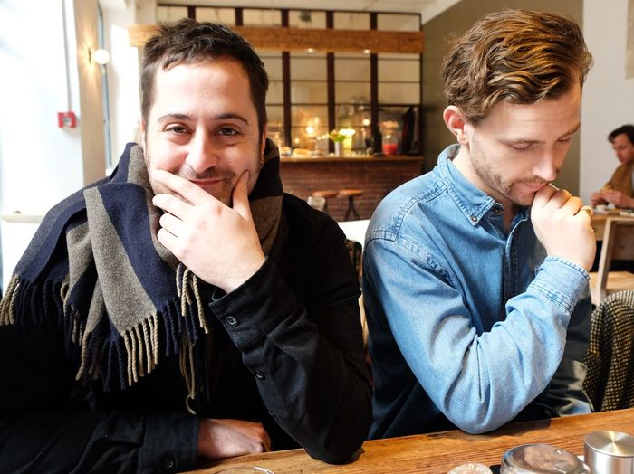 Portrait Of Two Men Sitting In Cafe
