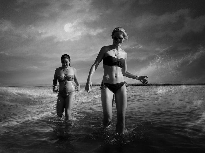 Women walking in sea against sky
