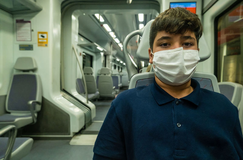 View of a boy wearing a mask inside a subway car in malaga during pandemic..