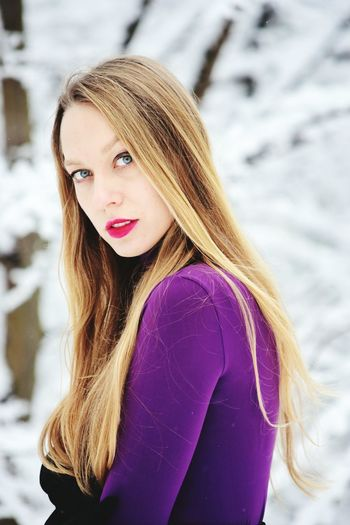 Portrait of young woman with blond hair standing outdoors during winter