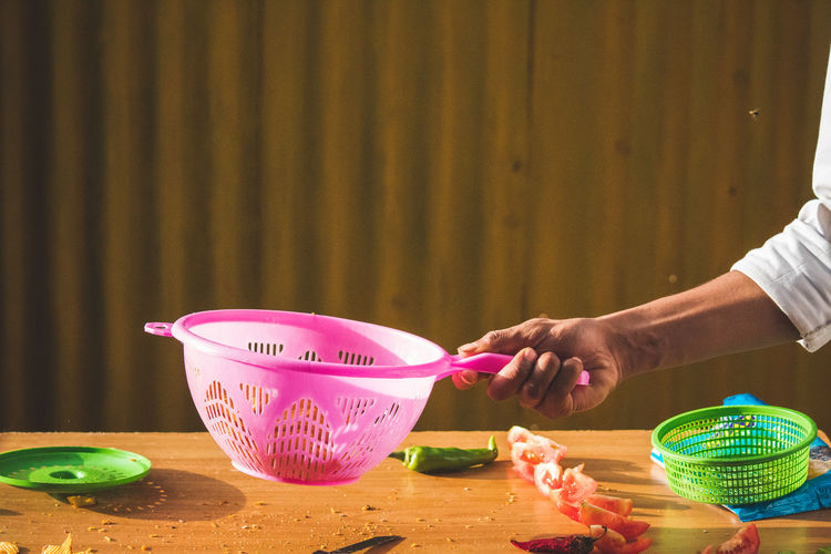 Cropped hand of person holding plastic colander at home