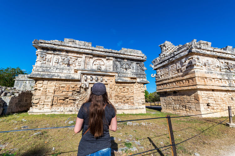 Rear View Of Woman Standing At Chichen Itza During Sunny Day