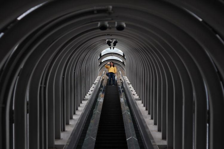 Low angle view of woman on escalator