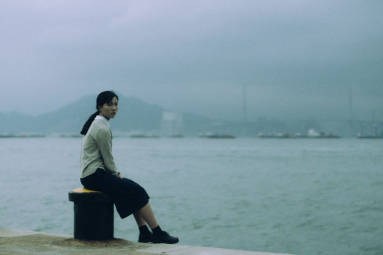Side view of young woman sitting on bollard in sea against sky