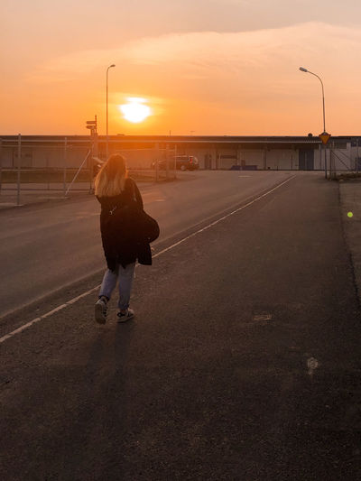 Rear view of woman on street against sky during sunset