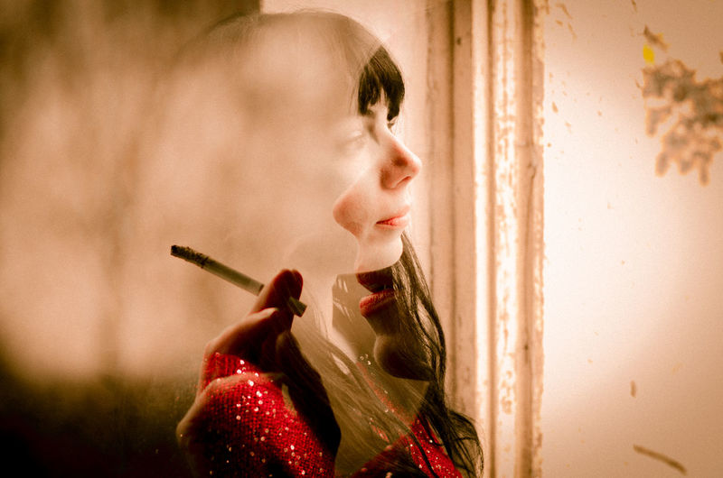 One Person One Young Woman Only Smoking Smoking Issues Thoughts View Window Woman In Red
