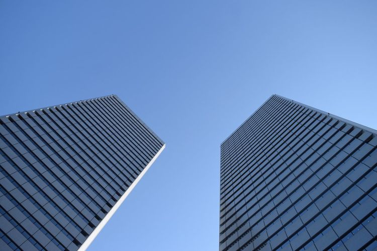 Tilted View Of Glass Buildings Against Clear Sky