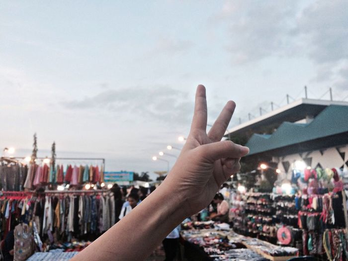 Close-up of hand showing peace sign at street market