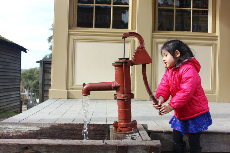Cute girl using hand pump