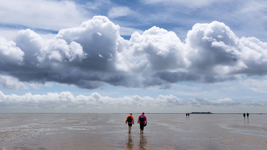 Rear View Of People At Beach Against Cloudy Sky
