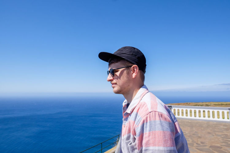 Close-up of young man looking at sea against clear blue sky