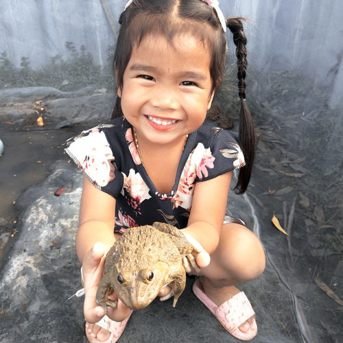 Portrait of smiling girl holding frog while crouching outdoors
