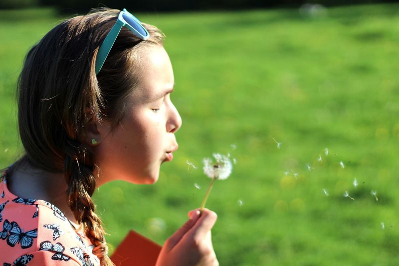 EyeEm Selects Blowing Dandelion Seed Head Focus On Foreground Real People Motion One Person Childhood Side View Girls Outdoors Water Flower Close-up Lifestyles Grass Nature Day Bubble Wand Freshness Dandelion Sunglasses