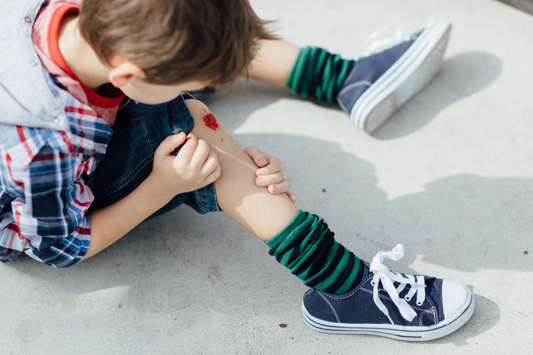High angle view of boy with wound on knee at skateboard park