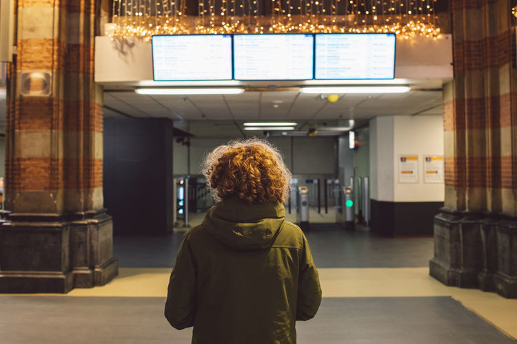 Rear view of woman standing in train station