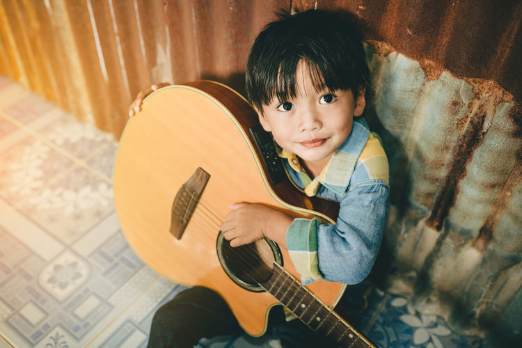 High Angle View Of Boy Playing Guitar