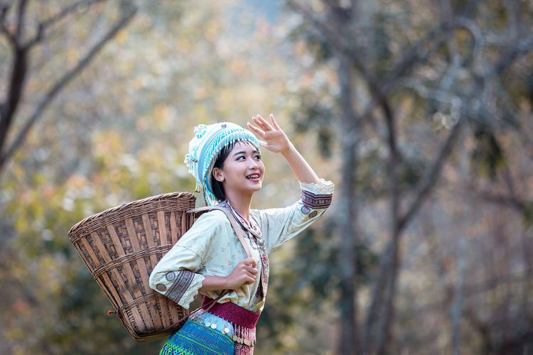 Young woman wearing Hmong traditional dress and enjoying in coffee garden at Doi Pui Chiang Mai Thailand. Women Young Adult Smiling One Person Young Women Clothing Beauty Standing Plant Focus On Foreground Tree Happiness Beautiful Woman Adult Human Arm Looking Looking Away Nature Fashion Arms Raised Limb Outdoors Human Limb Hairstyle Hmong