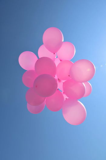 Low angle view of pink balloons against blue sky
