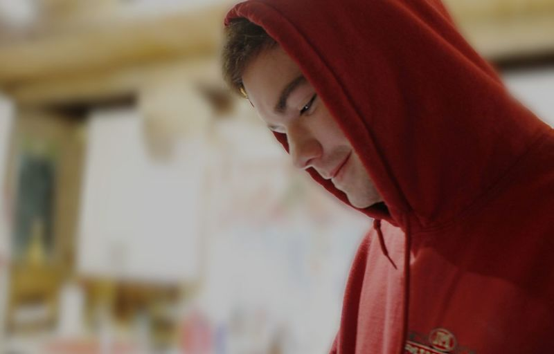 Close-up of smiling young man wearing hooded shirt